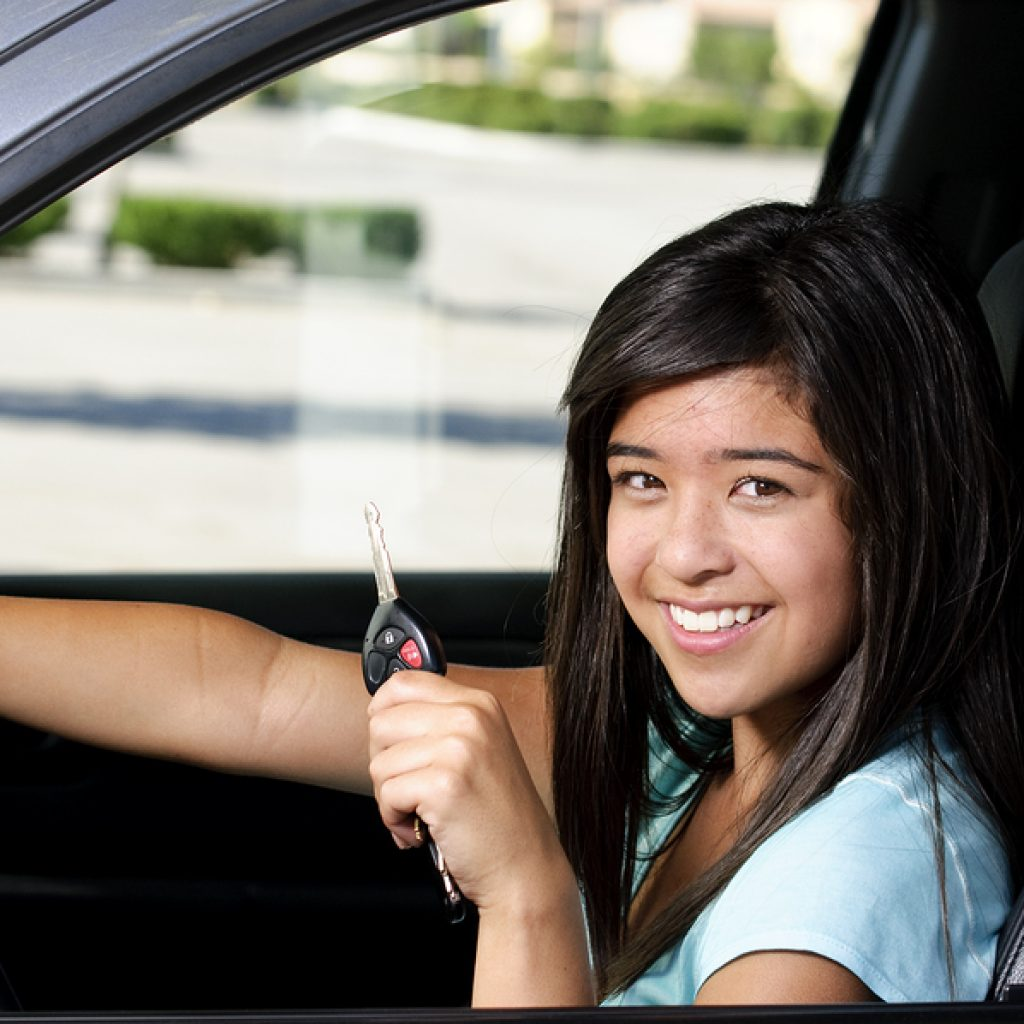 Photo of a teen driver: a 16 year old girl sitting in her new car as she holds her key and smiles